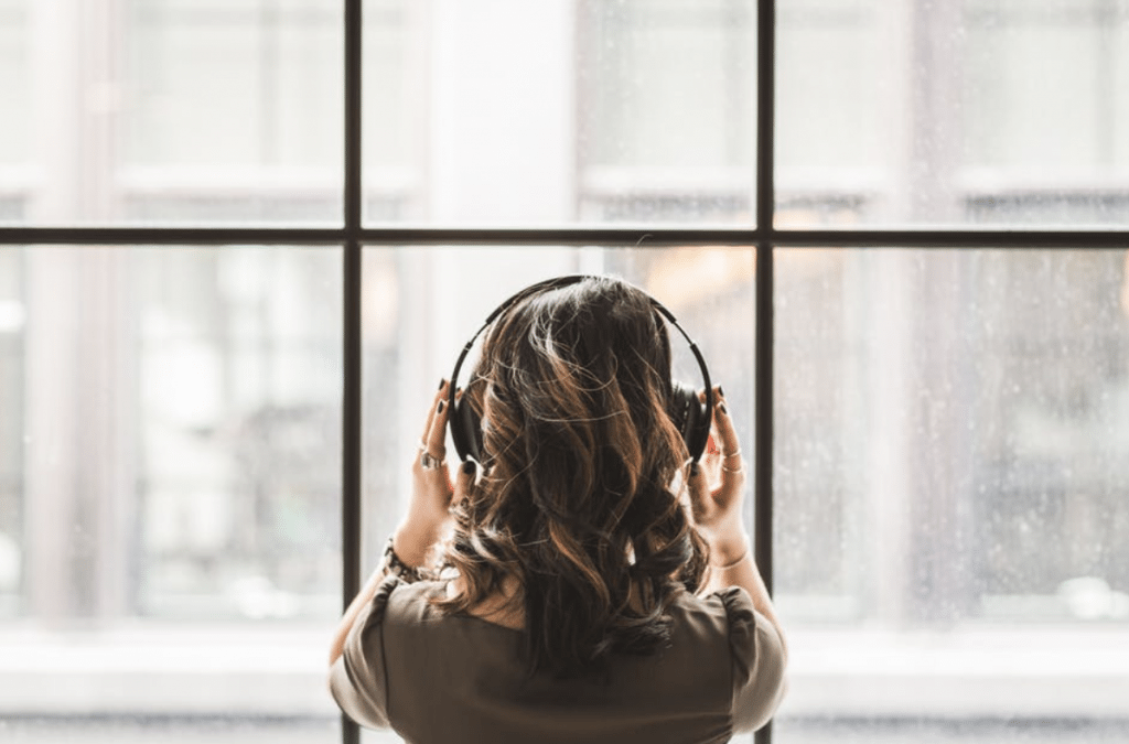 Woman in headphones in front of a large window