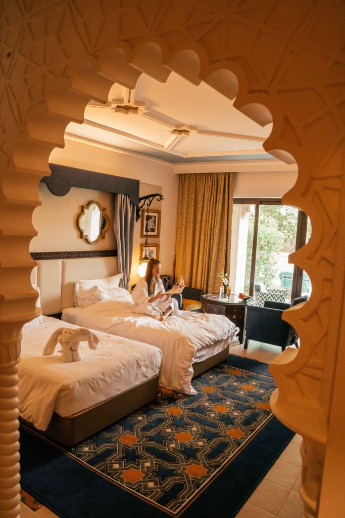 Arabian style room at Jumeirah Al Qasr Dubai with girl reading a magazine on the bed