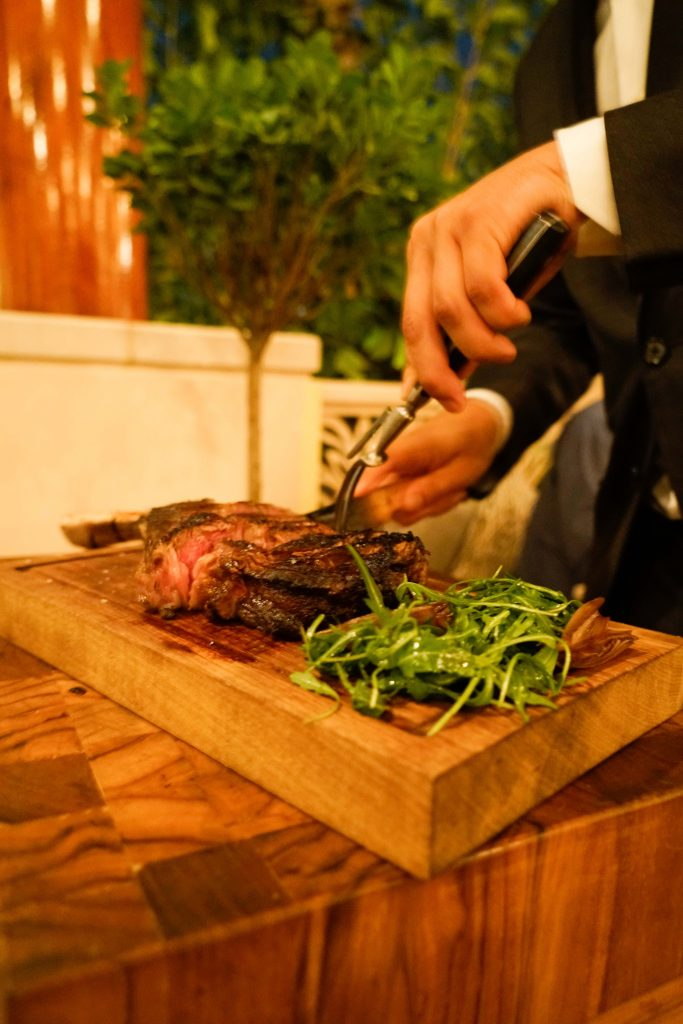Waiter cutting Tomahawk steak at The Hide