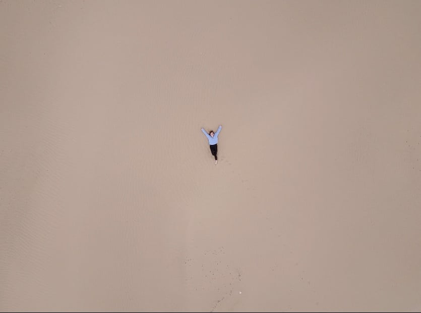 "Girl laying in the sand of ""mini Gobi"" desert in Mongolia"