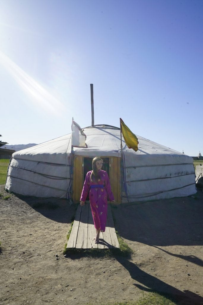 Girl in traditional Mongolian Del (outfit) walking out a yurt
