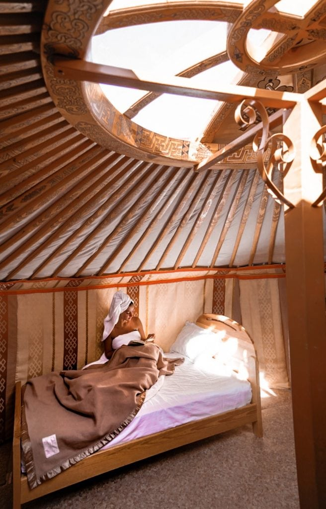 Girl reading a book in bed in a Mongolian yurt