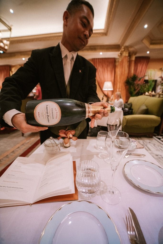 Waiter pouring champagne at The Dorchester Hotel London