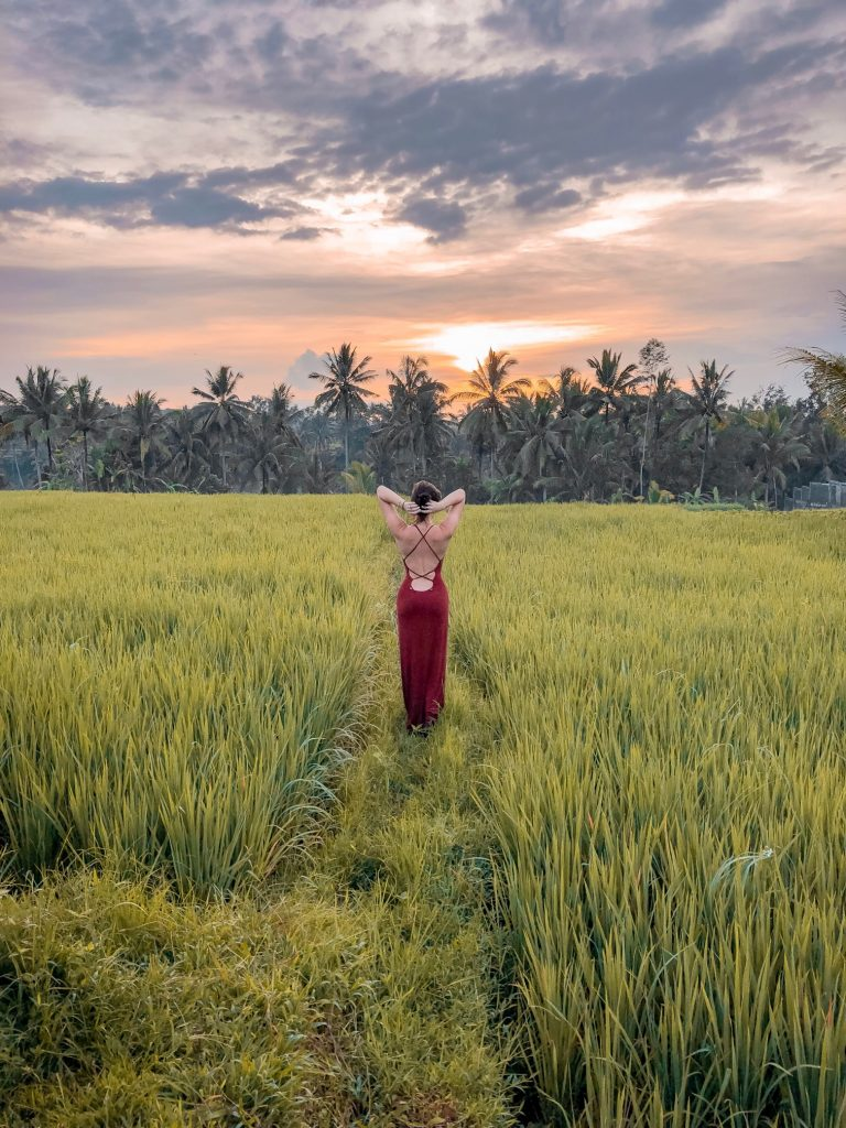 Girl in red dress watching the sunrise in Bali