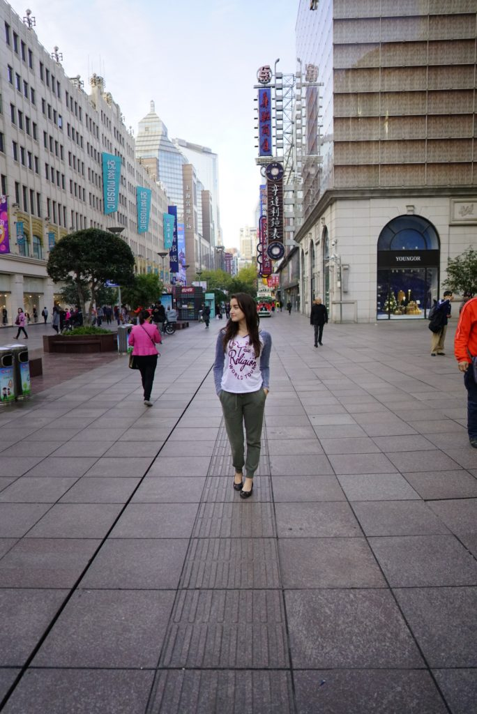 Elona Karafin standing on East Nanjing Road shipping district of Shanghai, China