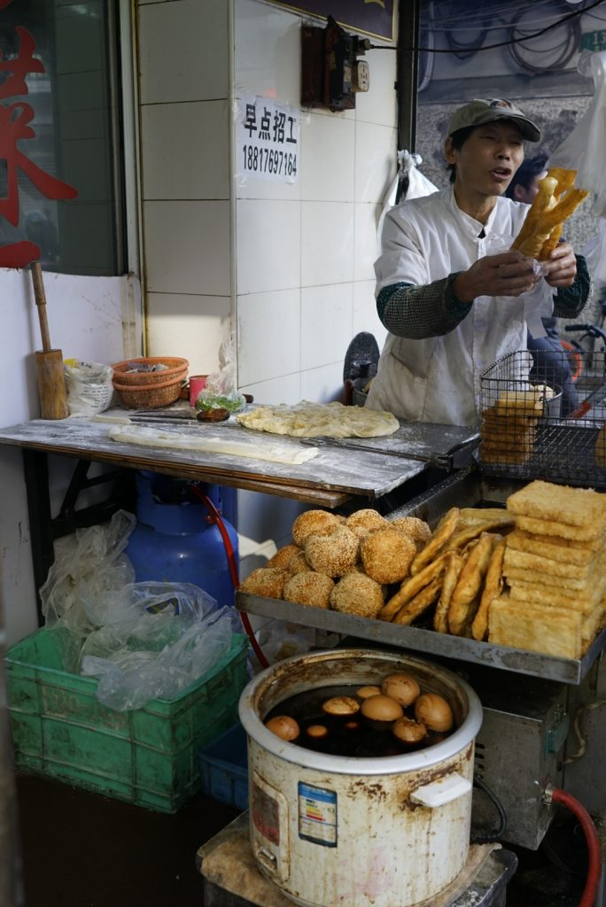 Man selling bread in an outdoor shop in Shanghai, China